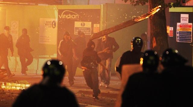 Manifestantes jogam pedaço de madeira em policiais em meio à revolta de jovens contra a exclusão social e desemprego que se espalhou pela Inglaterra em 2011.