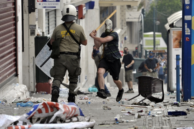 Em 28 de Junho, manifestante enfrenta polícia durante a greve geral de 48 horas deflagrada na Grécia.