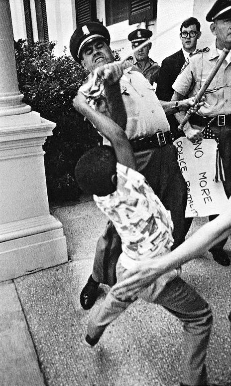 Policial arranca bandeira americana e cartaz contra a violência policial das mãos de um menino negro no contexto das lutas pelos direitos civis nos EUA.