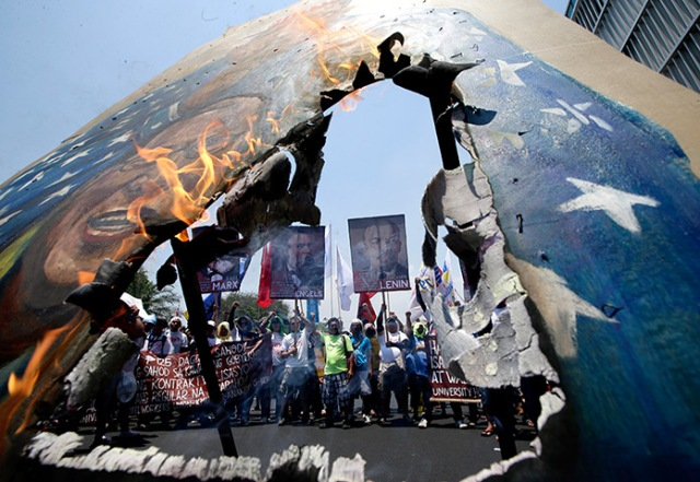 Protestantes incendeiam painel com as imagens de Obama e do Presidente Benigno Aquino III após serem impedidos de se aproximar da embaixada americana em Manila.