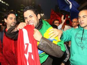 Enrolado em uma bandeira do Brasil, manifestante mastiga bandeira do PT (provavelmente retirada instantes antes das mãos de um militante).