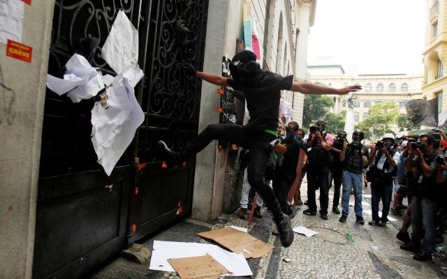 A demonstrator kicks an entrance of the Municipal Chamber during a teacher's strike in Rio de Janeiro