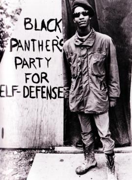 """Militante dos Panteras negras. A pintura na parede diz: """"Partido Panteras Negras para auto-defesa"""""""