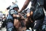 Mesmo depois de ser imobilizado pela polícia o manifestante continua sendo agredido.