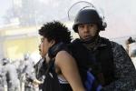 Manifestante preso levado por policial sem identificação.