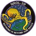 """O símbolo ofícial de um satélite de reconhecimento norte-americano: """"Nada está além do nosso alcance""""."""