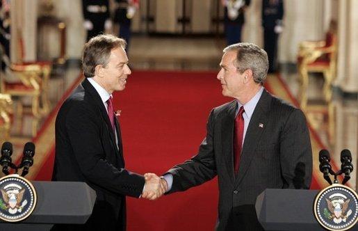 Tony Blair e George W. Bush apertam as mãos após a coletiva de imprensa dada no Salao Leste da Casa Branca em 12 de Novembro de 2004.